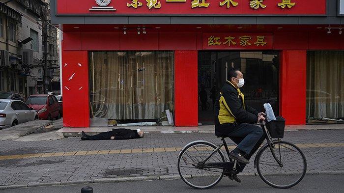 File foto ini diambil pada 30 Januari 2020 yang memperlihatkan seorang pria yang mengenakan sungkup muka melewati seorang lelaki tua pingsan dan meninggal di trotoar di sepanjang jalan dekat sebuah rumah sakit di Wuhan.