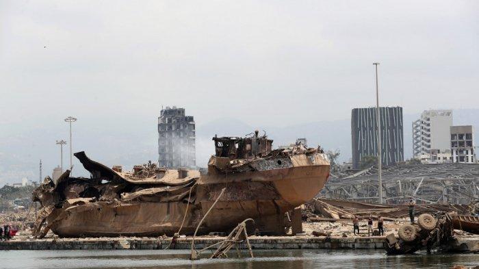 Orang-orang berdiri di dekat bangkai kapal di lokasi ledakan yang hancur di pelabuhan Beirut pada 6 Agustus 2020, dua hari setelah ledakan besar melanda ibu kota Lebanon dalam bencana yang memicu kesedihan dan kemarahan. Presiden Prancis mengunjungi Beirut yang dilanda gempa pada 6 Agustus, menjanjikan dukungan dan mendesak perubahan setelah ledakan besar menghancurkan ibu kota Lebanon dalam bencana yang menyebabkan 300.000 orang kehilangan tempat tinggal.