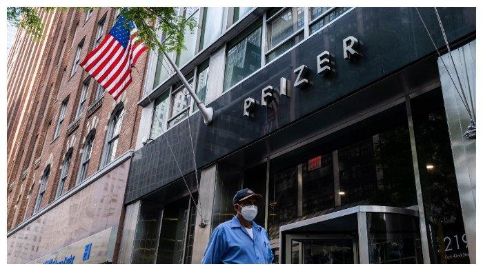 Seorang pria bermasker berjalan melewati markas perusahaan vaksin, Pfizer Inc., di New York, Amerika Serikat, pada Rabu (22 Juli 2020). Pfizer dan perusahaan bioteknologi Jerman, BioNTech, sepakat menyuplai Pemerintah AS dengan 100 juta dosis vaksin Covid-19 dalam kesepakatan senilai $1,95 miliar.