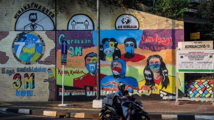 melintasi-mural-berisi-pesan-ajakan-menggunakan-masker.jpg