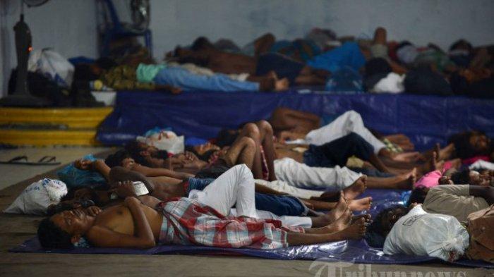 Migran diselamatkan sebagian besar Rohingya dari Myanmar dan Bangladesh tidur di balai desa di kota nelayan Pangkalan Susu, Kabupaten Langkat Propinsi Sumatera Utara pada 16 Mei 2015 setelah 95 diselamatkan oleh nelayan lokal Indonesia dari laut lepas Pangkalan Susu. AFP PHOTO / ROMEO GACAD