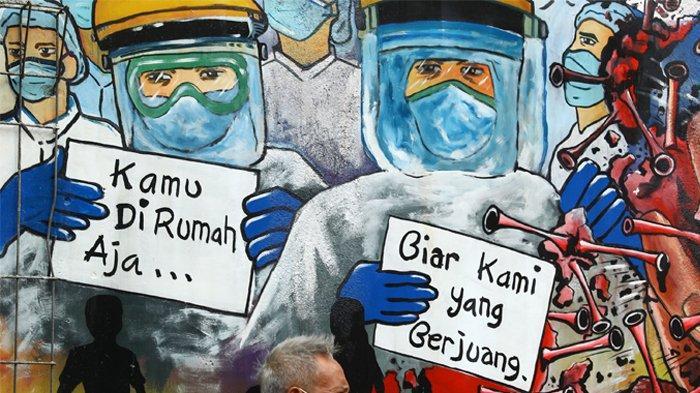 Warga berada di depan mural yang bergambar dukungan untuk tenaga medis yang ada di Kavling Kinayung Pondok Aren, Tangerang Selatan, Banten, Jumat (22/5/2020). Mural yang dibuat oleh warga itu bertujuan untuk memberikan dukungan dan apresiasi atas perjuangan tenaga medis yang menjadi garis terdepan dalam penanganan COVID-19.