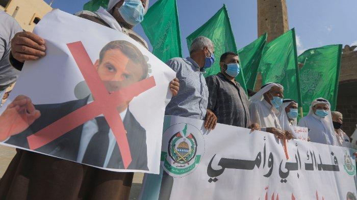 Demonstran Palestina mengangkat bendera dan plakat dalam unjuk rasa memprotes komentar Presiden Prancis Emmanuel Macron atas kartun Nabi Muhammad, di Deir al-Balah di Jalur Gaza tengah, pada 25 Oktober 2020.