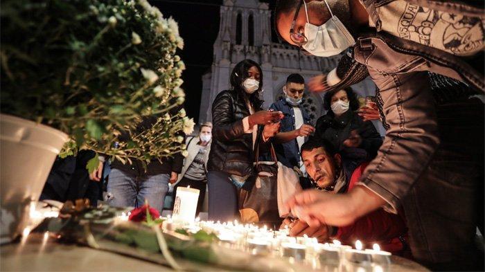 Sejumlah warga menyalakan lilin di luar Basilika Notre-Dame de l'Assomption di Nice pada tanggal 29 Oktober 2020 untuk menghormati tiga korban penyerang pisau, yang memotong tenggorokan setidaknya satu wanita, di dalam gereja di kota French Riviera.