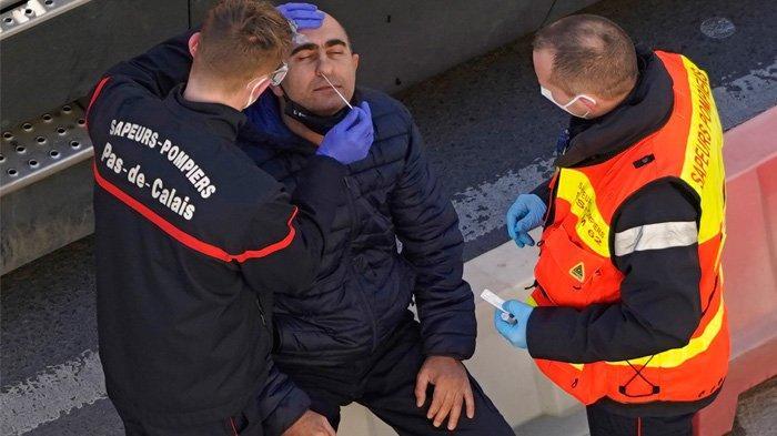 Anggota Dinas Pemadam Kebakaran Prancis memeriksa pengemudi truk untuk tes COVID-19 di Pelabuhan Dover, di Dover di pantai tenggara Inggris, pada 25 Desember 2020, saat pengujian COVID-19 terhadap pengemudi yang mengantri untuk berangkat dari terminal feri ke Eropa berlanjut. Sekelompok ilmuwan di Inggris sedang menguji coba obat antibodi baru untuk mencegah penularan virus Covid-19.
