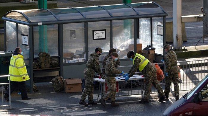 Perwira Angkatan Darat Inggris bekerja dengan penguji NHS & Tesr dan Trace Covid-19 di Pelabuhan Dover, di Dover di pantai tenggara Inggris, pada 25 Desember 2020, saat pengujian Covid-19 terhadap pengemudi yang mengantri untuk berangkat dari terminal feri ke Eropa terus berlanjut. Sekelompok ilmuwan Inggris sedang mengujicoba obat terbaru antibodi yang diharapkan dapat memberikan kekebalan instan dan menyelamatkan ribuan nyawa bila obat ini sukses melewati ujicoba.