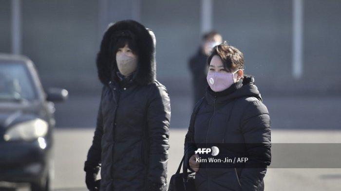 Orang-orang mengenakan masker saat berjalan di daerah Pyongyang, Korea Utara, 6 Februari 2020. (KIM WON-JIN/AFP)