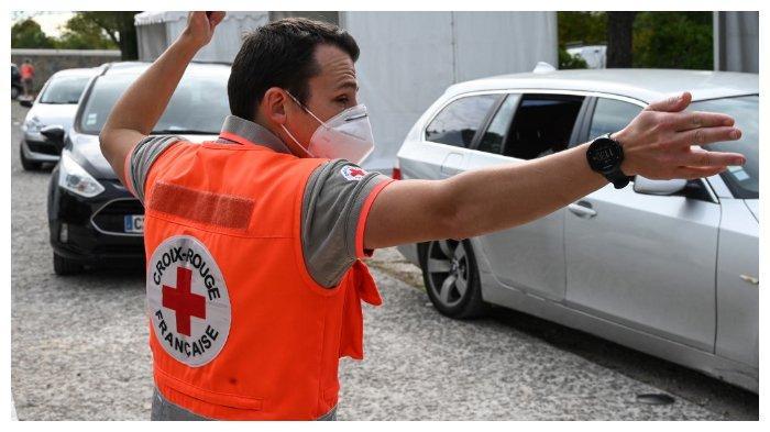 ILUSTRASI - Seorang anggota Palang Merah Prancis yang menggunakan masker sedang mengatur mobil yang ada di tempat tes Covid-19 secara drive-through pada 14 Oktober 2020 di Montpellier. Prancis saat ini mengalami lonjakan kasus Covid-19.