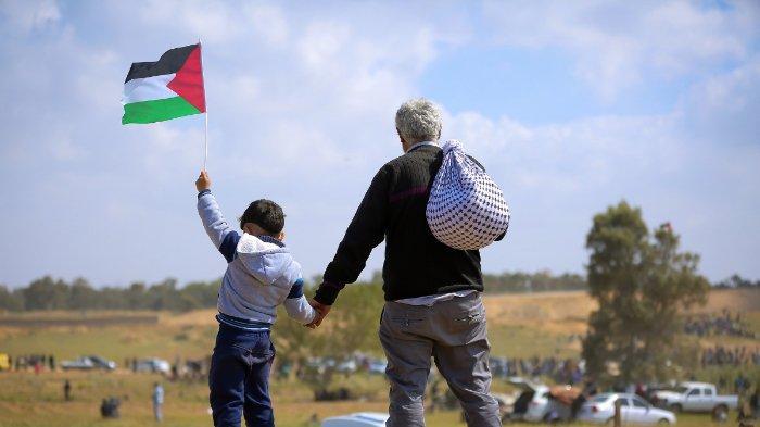 ILUSTRASI - FOTO: Seorang pria menggandeng tangan anak kecil yang membawa bendera Palestina