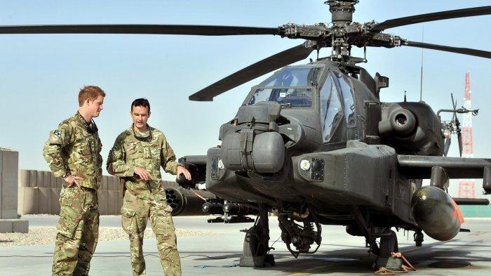 Pangeran Kerajaan Inggris, Harry (kiri) ditunjukkan Apache penerbangan-line oleh anggota skuadron di Camp Bastion di Provinsi Helmand, Afghanistan. Jum'at (7/9/2012) (tribunnews.com)