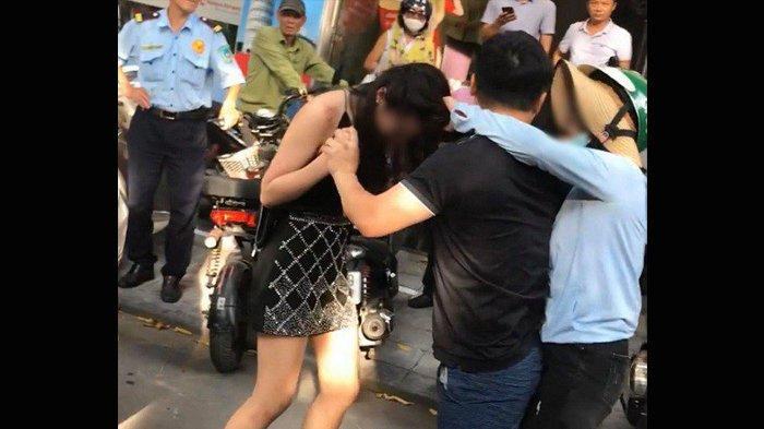 Suami ini berusaha melerai perkelahian antara istri dan selingkuhannya yang menjadi tontonan warga di jalanan.