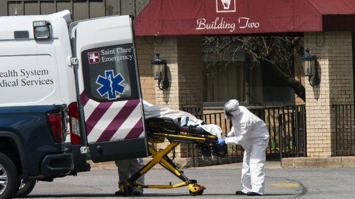 Pekerja medis memasukkan mayat ke dalam ambulans sambil mengenakan masker dan alat pelindung diri (APD) di Pusat Subakut dan Rehabilitasi Andover pada 16 April 2020 di Andover, New Jersey. Setelah mendapatkan laporan anonim di kepolisian, 17 orang ditemukan tewas di fasilitas perawatan jangka panjang, termasuk dua perawat, di mana setidaknya 76 pasien dan 41 anggota staf telah dinyatakan positif COVID-19.