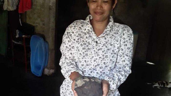 Isteri Josua Hutagalung menunjukkan bongkahan batu yang diduganya benda langit (meteor) yang jatuh menimpa kediamannya di Dusun Sitahan Barat, Desa Satahi Nauli, Kecamatan Kolang, Kabupaten Tapanuli Tengah, Sabtu (1/8/2020).
