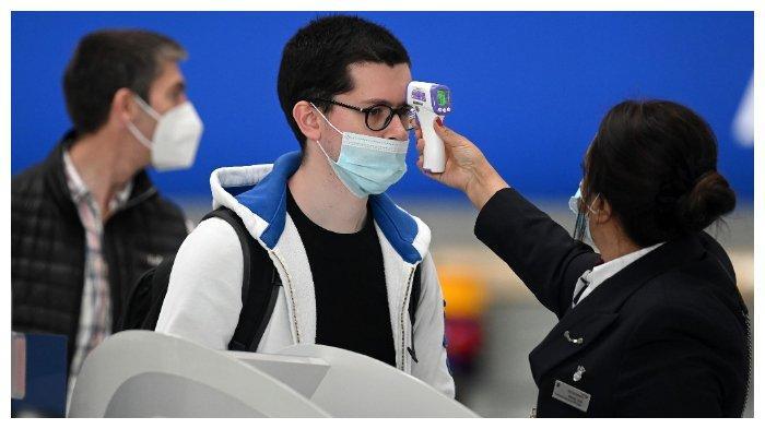 ILUSTRASI - Penumpang bermasker dicek suhu tubuhnya di Bandara Heathrow, London bagian barat, 10 Juli 2020. Inggris mungkin akan memperlama periode karantina untuk mereka yang baru pulang dari luar negeri.