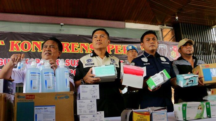 Kabid Humas Polda Jateng, Kombes Pol Iskandar F Sutisna (kedua kiri) bersama petugas kepolisian dari Ditreskrimum Polda Jawa Tengah menunjukkan masker dan hand sanitizer sitaan saat melakukan gelar atas penangkapan penimbun masker dan hand sanitizer di halaman Polda Jateng, Kota Semarang, Jawa Tengah, Selasa (4/3/2020). Polisi mengamankan barang bukti berupa 4.000 masker dan 208 botol hand sanitizer. Menurut Iskandar F Sutisna, penangkapan tersangka berawal dari patroli siber saat masker mengalami kelangkaan di pasaran dan ada indikasi beberapa pihak yang memanfaatkan situasi dengan cara melakukan penimbunan. Tribun Jateng/Hermawan Handaka