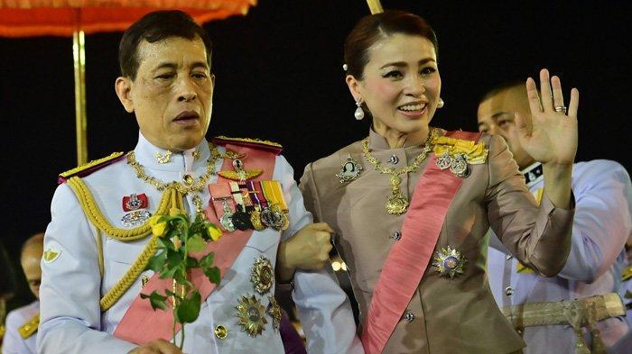 Ratu Suthida menggandeng tangan Raja Thailand Maha Vajiralongkorn dan saat melambaikan tangan ke para pendukung royalis yang berkerumun di depan Grand Palace, Bangkok, Jumat 23 Oktober 2020. (Lillian SUWANRUMPHA / AFP)