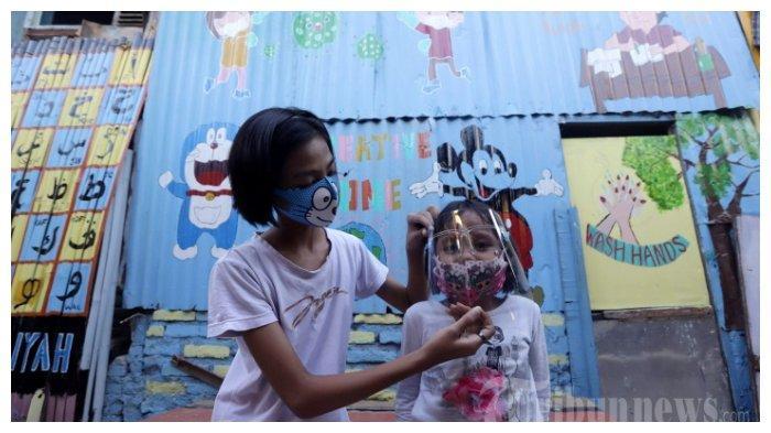 Anak-anak bermain dengan latar belakang mural bertemakan Covid-19 di lapangan bulu tangkis Kampung Kali Pasir, Jakarta Pusat, Senin (27/7/2020). Jumlah kasus positif Covid-19 di Indonesia kini sudah menembus angka 100 ribu kasus.