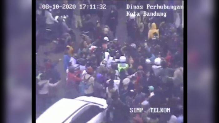 Rekaman CCTV polisi dikepung massa di pertigaan Jalan Sentot Alibasyah-Jalan Surapati namun berhasil diselamatkan oleh seorang mahasiswa beralamater saat demo tolak UU Cipta Kerja.
