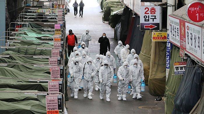 Pekerja pasar mengenakan disinfektan semprotan pelindung di sebuah pasar di kota tenggara Daegu pada 23 Februari 2020 sebagai tindakan pencegahan setelah wabah coronavirus COVID-19. (YONHAP / AFP)