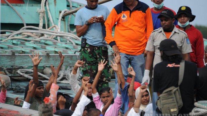 ILUSTRASI - Sekelompok migran diselamatkan, sebagian besar Rohingya dari Myanmar dan Bangladesh, mengangkat tangan mereka saat tiba di daerah kurungan baru di kota nelayan Kuala Langsa di Aceh pada 15 Mei 2015. Lebih dari 750 Rohingya dan migran Bangladesh diselamatkan pada tanggal 15 Mei. AFP PHOTO / Chaideer MAHYUDDIN