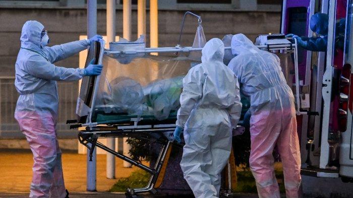 Para pekerja medis membawa seorang pasien di bawah perawatan intensif ke rumah sakit sementara Columbus Covid 2 yang baru dibangun  pada 16 Maret 2020 untuk para pasien coronavirus di Gemelli di Roma.