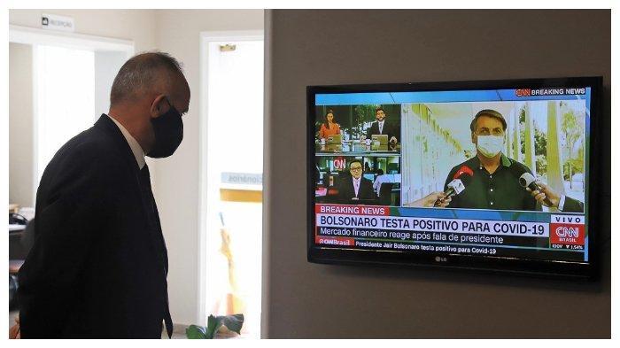 Seorang pekerja rumah pemakaman menonton siaran langsung yang memperlihatkan Presiden Brazil Jair Bolsonaro mengumumkan dirinya positif terjangkit Covid-19, (7/7/2020)