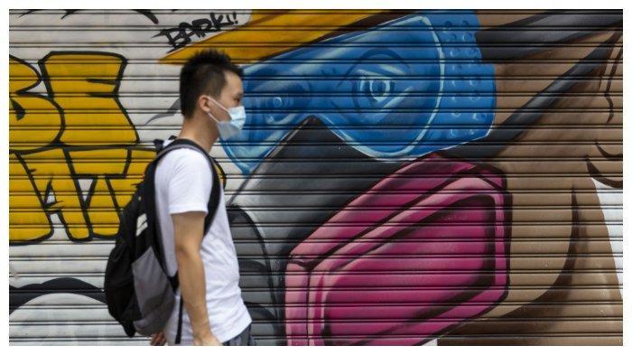 Seorang pria yang menggunakan masker untuk mencegah Covid-19, sedang berjalan di jalan Hong Kong pada 23 Agustus 2020.