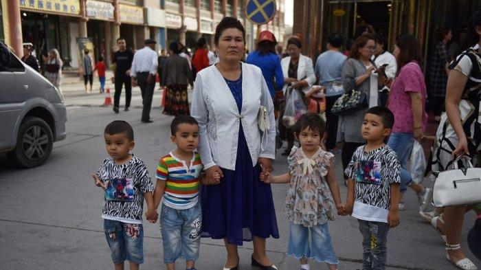 Foto ini diambil pada 4 Juni 2019 menunjukkan seorang wanita Uighur bersama dengan anak-anak di sebuah jalan di Kashgar di wilayah Xinjiang barat laut Cina. Otoritas China melakukan sterilisasi paksa terhadap perempuan dalam operasi menahan pertumbuhan populasi etnis minoritas di wilayah Xinjiang barat, menurut penelitian yang diterbitkan pada 29 Juni 2020.