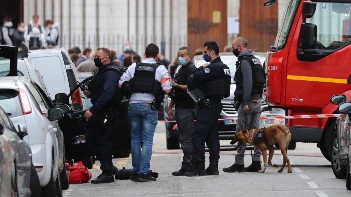 FOTO: Seorang petugas polisi dan anjing pelacak terlihat menggeledah mobil yang diparkir di dekat Basilika Notre-Dame de Nice, setelah insiden serangan teror pelaku yang membawa pisau di Nice pada 29 Oktober 2020.
