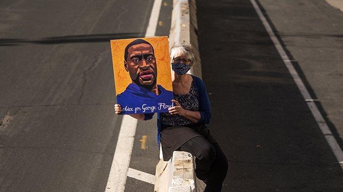 Margie O'Loughlin memegang potret George Floyd di luar Pusat Pemerintah Kabupaten Hennepin pada tanggal 5 April 2021 di Minneapolis, Minnesota. Sidang pembunuhan Derek Chauvin berlanjut hari ini, mantan petugas Kepolisian Minneapolis dituduh melakukan berbagai tuduhan pembunuhan dalam kematian George Floyd Mei lalu.