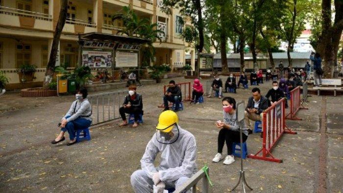 Penduduk, yang memakai masker wajah sebagai tindakan pencegahan terhadap penyebaran virus corona COVID-19, mempraktikkan social distancing ketika mereka menunggu untuk diuji di pusat pengujian cepat sementara dekat rumah sakit Bach Mai di Hanoi pada 31 Maret 2020.
