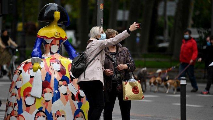 FOTO: Orang-orang yang sedang memakai masker berswafoto di depan patung