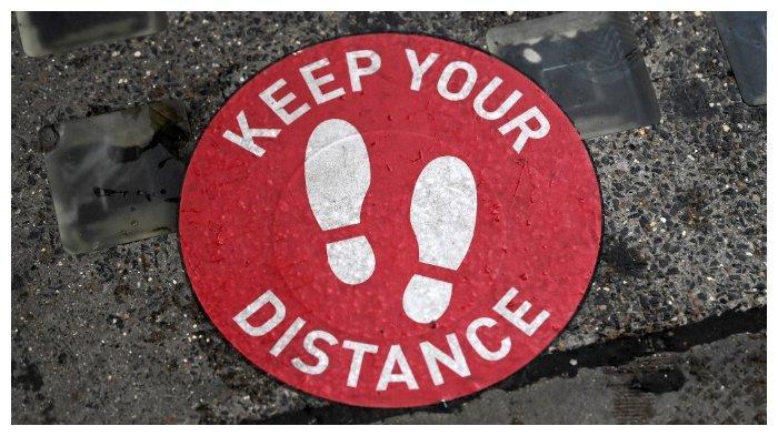 Sebuah stiker di trotoar di Inggris mengingatkan pejalan kaki untuk tetap menjaga jarak.