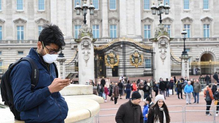ILUSTRASI - Antisipasi penyebaran virus corona, pemilihan lokal di Inggris terpaksa harus ditunda selama setahun hingga Mei 2021. Foto: Seorang pria menggunakan masker di depan Istana Buckingham