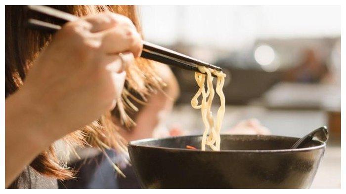Ilustrasi seorang perempuan sedang memakan mie menggunakan sumpit.