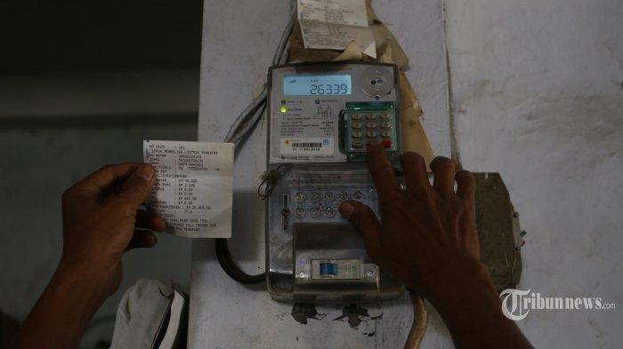 Dedi Muhtadi, seorang warga Kramat, Senen, Jakarta Pusat, tengah mengisi token listrik ke meteran listrik, Selasa (8/9/2015).