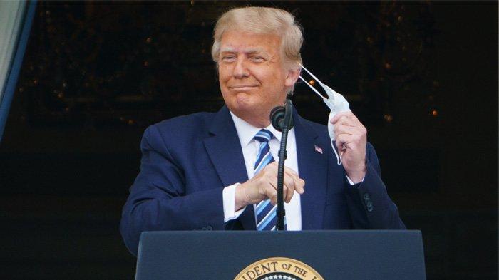 Presiden AS Donald Trump melepas maskernya sebelum berbicara pada rapat umum dari South Portico Gedung Putih di Washington, DC pada 10 Oktober 2020.