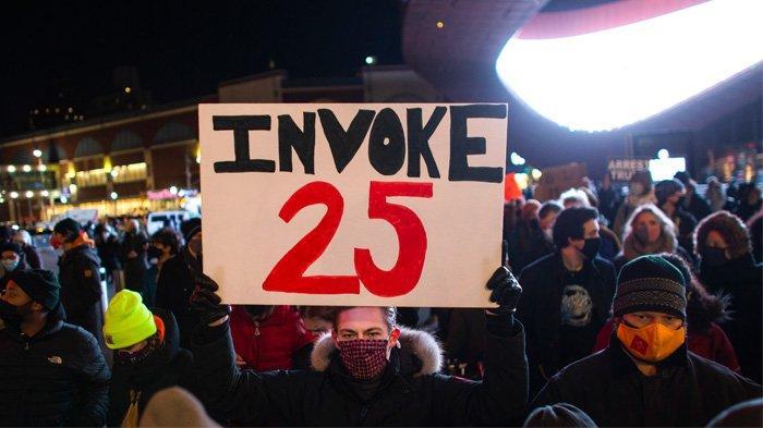 Seorang demonstran memegang tanda menyerukan Amandemen ke-25 untuk mencopot Presiden AS Donald Trump dari jabatannya selama protes di luar Barclays Center di Brooklyn, New York pada 7 Januari 2021 sehari setelah massa pro-Trump menyerbu dan menghancurkan Capitol. Presiden Donald Trump menghadapi seruan yang terus meningkat pada 7 Januari untuk dicopot dari jabatannya berdasarkan Amandemen ke-25 karena menghasut kekerasan massa yang melanda Capitol AS satu hari sebelumnya.