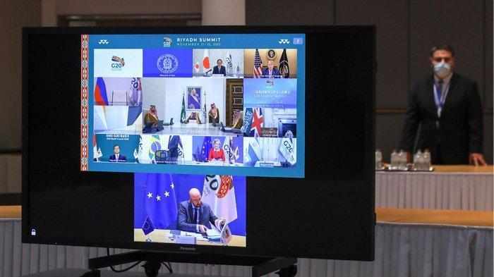 Perdana Menteri Jepang Yoshihide Suga (kiri atas), Presiden AS Donald Trump (kanan atas), Raja Arab Saudi Salman bin Abdulaziz Al Saud (tengah), Presiden Korea Selatan Moon Jae-in (baris ke-3, kiri), Presiden Komisi Eropa Ursula von der Leyen (baris ke-3, kanan), dan Presiden Dewan Eropa Charles Michel (bawah), terlihat di layar sebelum dimulainya KTT G20 virtual yang diselenggarakan oleh Arab Saudi dan diadakan melalui konferensi video di tengah Covid-19 (novel coronavirus) pandemi, di Brussel, pada 21 November 2020. - Arab Saudi menjadi tuan rumah KTT G20 pada 21 dan 22 November, yang pertama untuk negara Arab, dengan forum virtual didominasi oleh upaya untuk mengatasi pandemi virus corona dan resesi global terburuk di dekade.