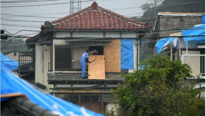 Para lelaki menempelkan papan kayu lapis ke dinding yang dirusak oleh benda-benda terbang ketika Topan Faxai melanda pada bulan September, dalam persiapan untuk Typhoon Hagibis yang kuat di kota Prefektur Tateyama, timur Tokyo, pada 11 Oktober 2019. (Mainichi / Koichiro Tezuka )