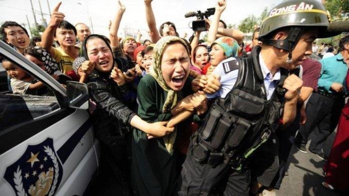 Sekelompok orang Uighur menghalau polisi dalam aksi protes di Provinsi Xinjiang, China.
