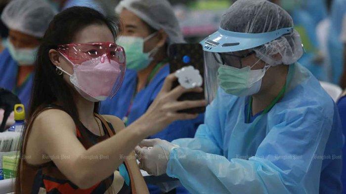 Seorang wanita berfoto selfie saat disuntik vaksin Covid-19 di Bang Sue Grand Station di distrik Chatuchak, Bangkok, Thailand pada Senin (7/6/2021)