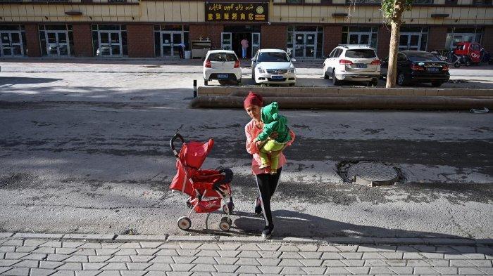 Wanita Uighur menggendong bayi di Xinjiang, Rabu (11/11/2019).