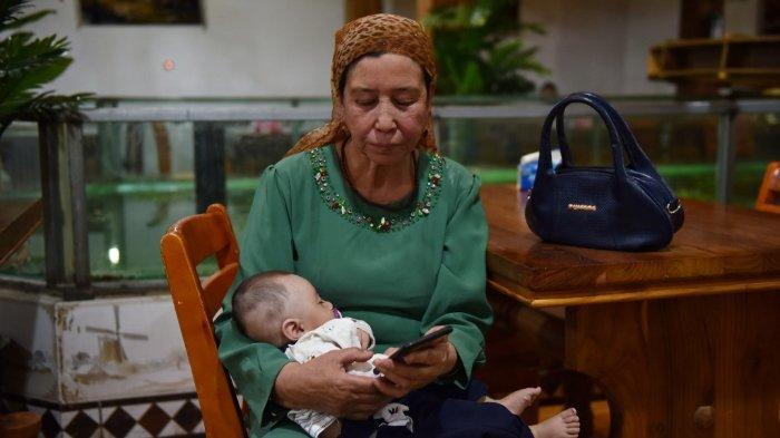 Wanita Uighur menggendong bayi, Jumat (31/5/2019).