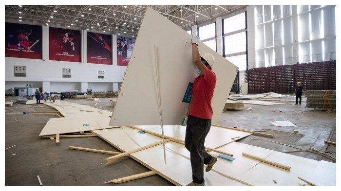 Seorang pekerja mengangkat papan ketika instalasi di rumah sakit darurat terbesar di Wuhan, Hubei, China, yang digunakan untuk merawat pasien Covid-19 dibongkar, 29 Juli 2020.