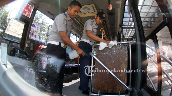 FOTO : Petugas Dishub Sterilisasi Bus Trans Metro Pekanbaru Cegah Penyebaran Virus Corona - bus-tmp-dibersihkan1.jpg