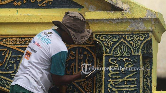Pekerja tengah mengecat tulisan kaligrafi pada pintu gerbang Masjid Raya di Senapelan Pekanbaru, Minggu (13/9/2020).