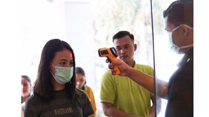 Pemeriksaan suhu tubuh di Mal Pekanbaru oleh petugas kepada pengunjung mal.