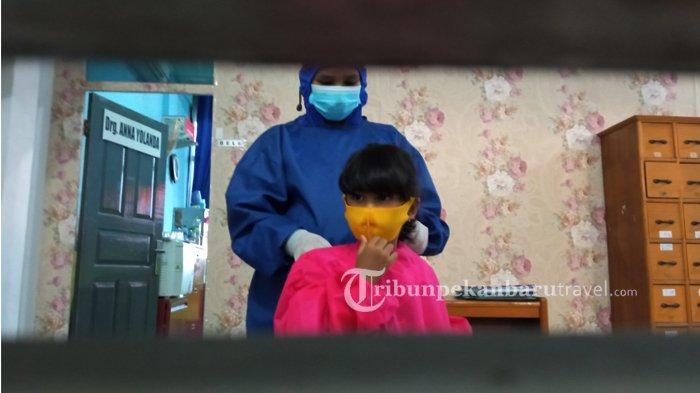 Seorang anak yang merupakan pasien dokter gigi menggunakan alat pelindung diri ( APD ) saat melakukan pengobatan di sebuah klinik gigi di Pekanbaru , Senin (28/2/2021).