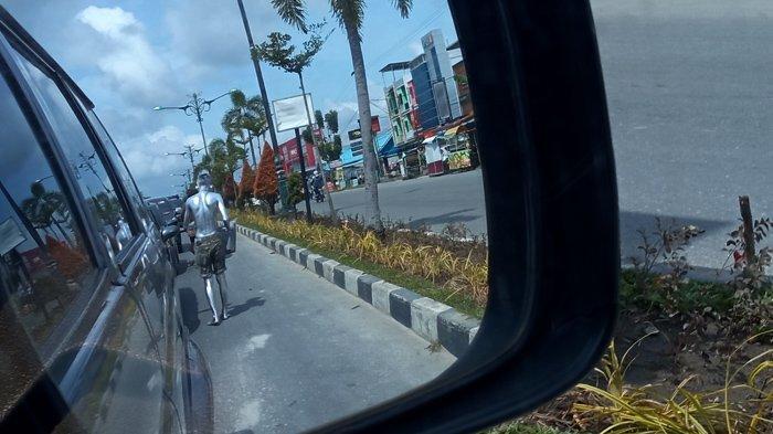 Seorang manusia silver beraksi di lampu merah Jalan Yos Sudarso Pekanbaru, Minggu (6/12/2020).